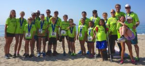 A team of 22 adults and children in matching neon lime green t-shirts stand smiling on the beach wearing medals around their necks from the Santa Barbara Triathlon